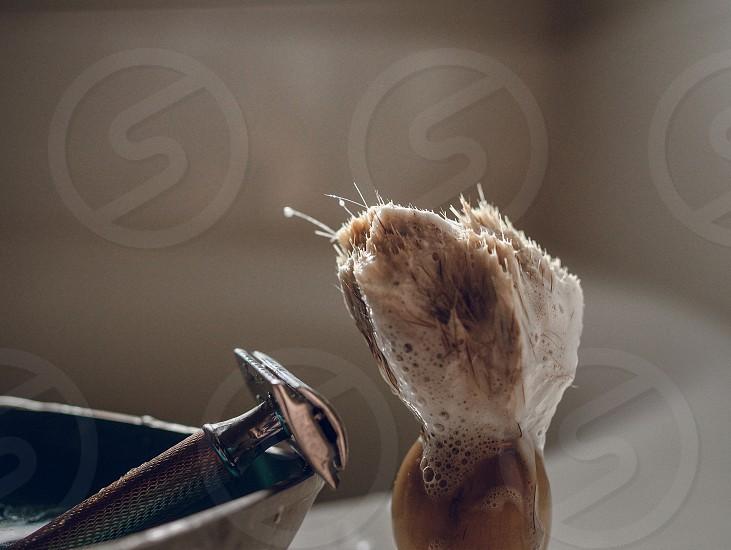 A safety razor and a shaving brush.  photo