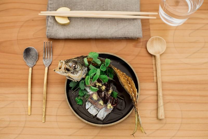 brown chopsticks on gray textile near on black fried fish bone photo