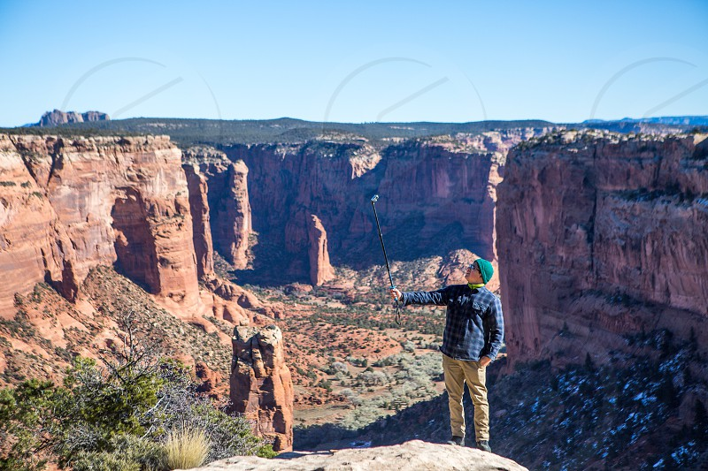 Thanksgiving vacation young man taking a picture with a selfie stick over canyon de chelly national park Arizona photo