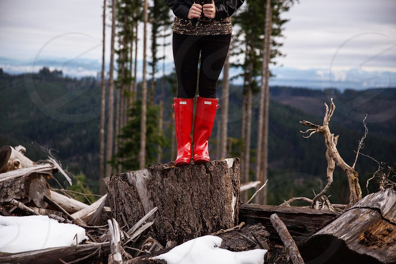 woman wearing red rain boots standing in top of brown wooden scrap photo
