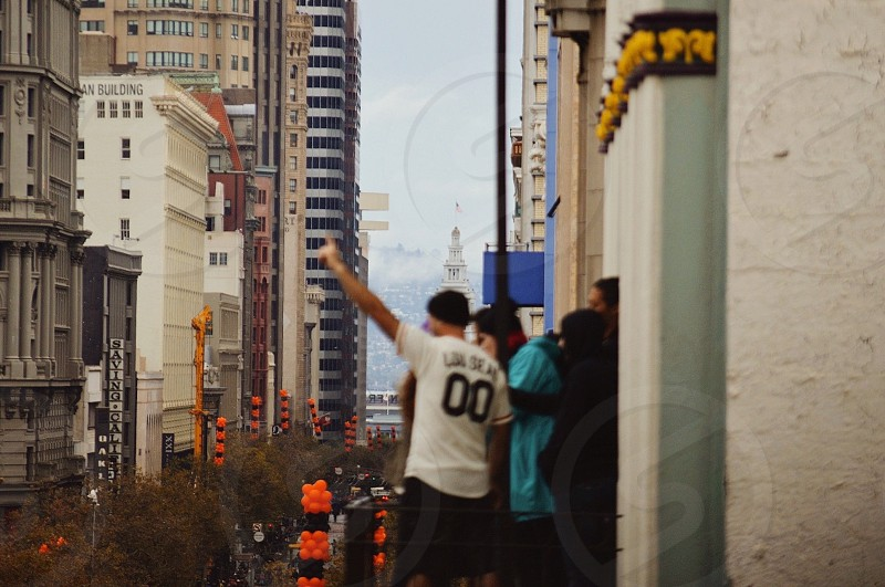 people standing on balcony of white gray and gold building overlooking city street photo