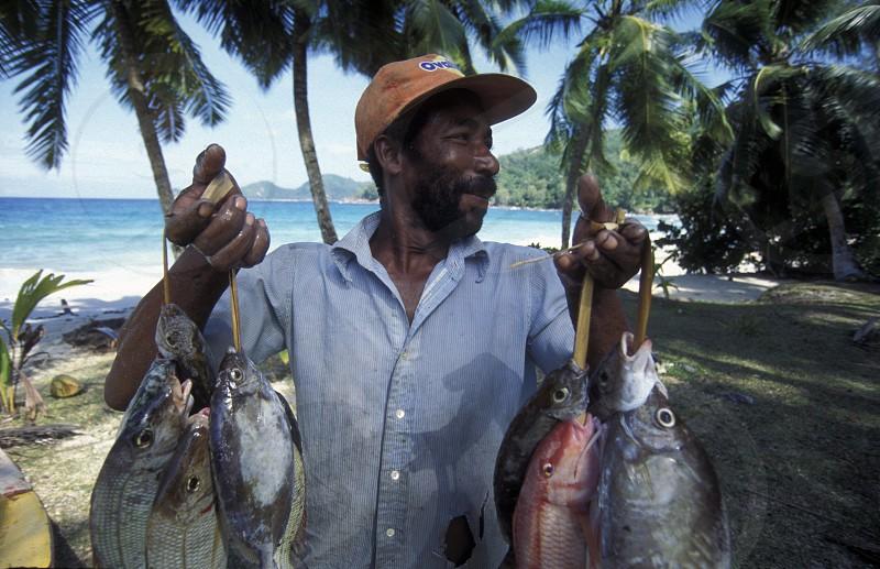a fishingmen on the Island Praslin of the seychelles islands in the indian ocean photo