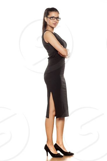 beautiful young woman in a tight black dress posing on a white photo