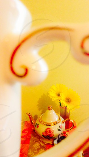 white and gold ceramic teapot near yellow flowers photo