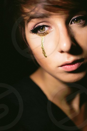 woman with gold glitters on her right cheek photo