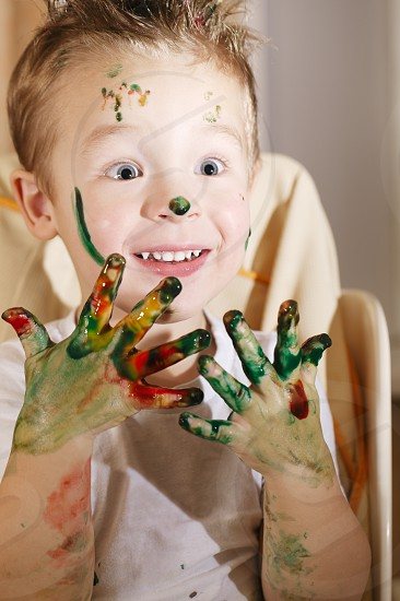 Cute excited small boy with his hands full of colorful splodges of finger paint holding them up in front of him with big eyes full of amazement photo