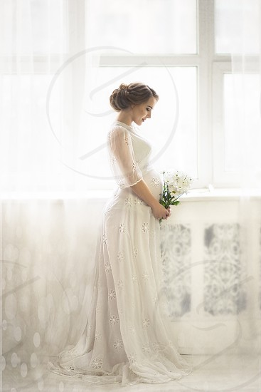 pregnant woman stands by the window and looks at a bouquet of flowers photo