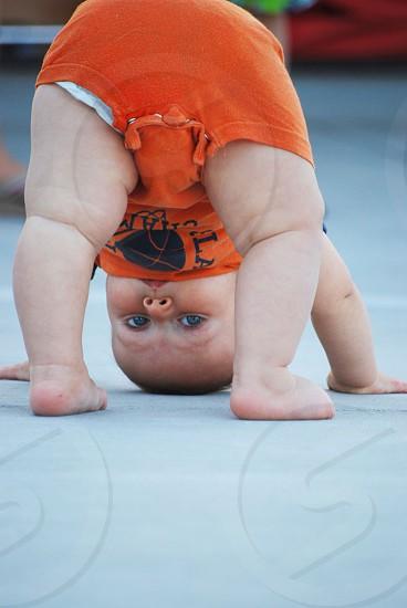 baby in orange shirt bending photo