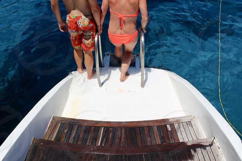 Young couple on a boat with swimwear during summer in Ayia Napa Cyprus photo
