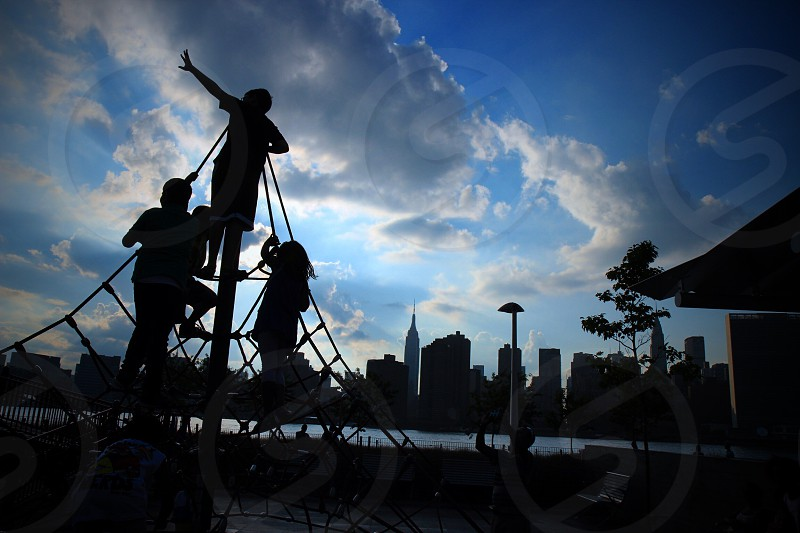 Kids in playground overlooking Manhattan Skyline silhouette.  photo