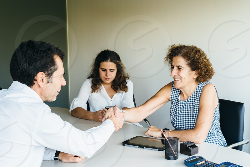 Businessman and businesswoman handshaking across conference table in  meeting photo
