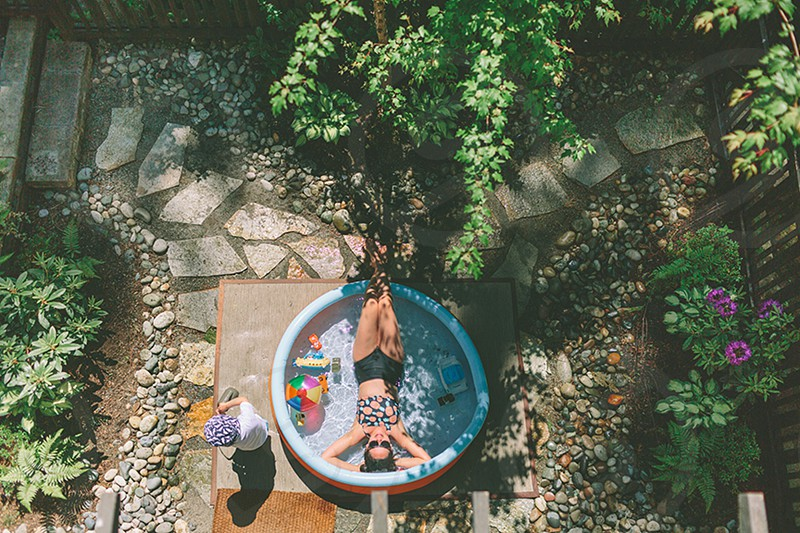 A woman relaxing in a small pool in the backyard. photo