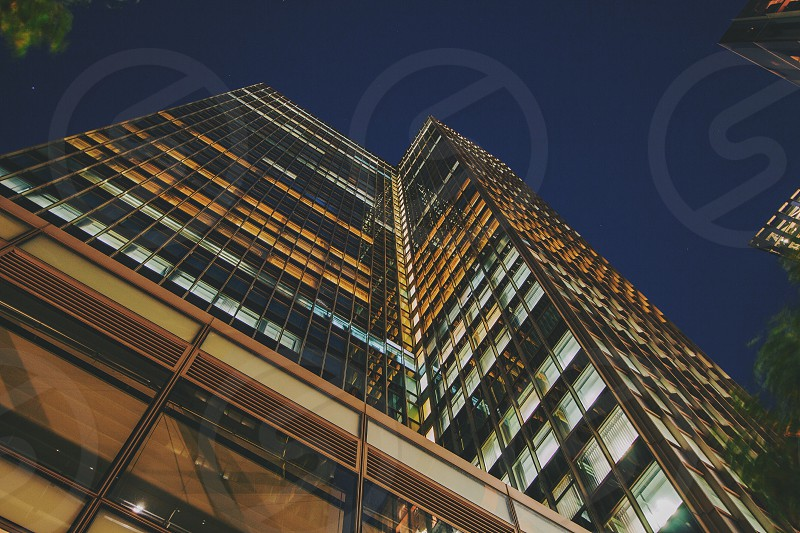 low angle photography of a building with lights turned on at night photo