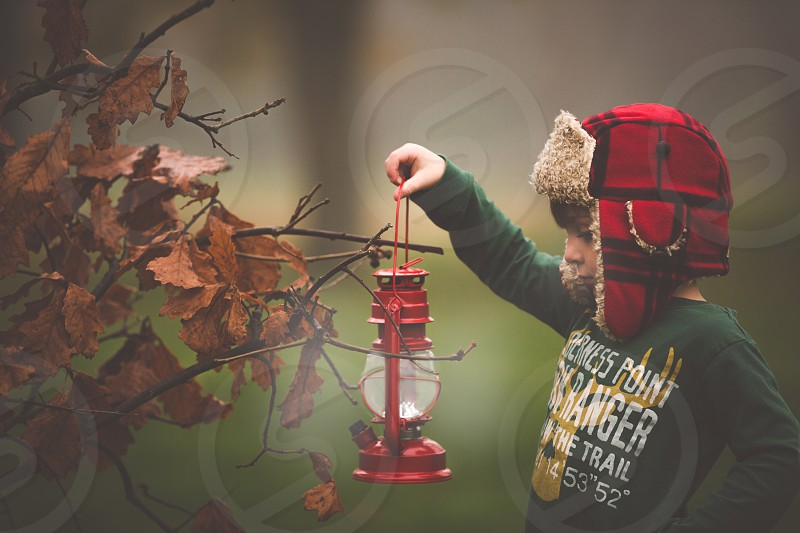 Young boy holding red lantern in the fog.   photo