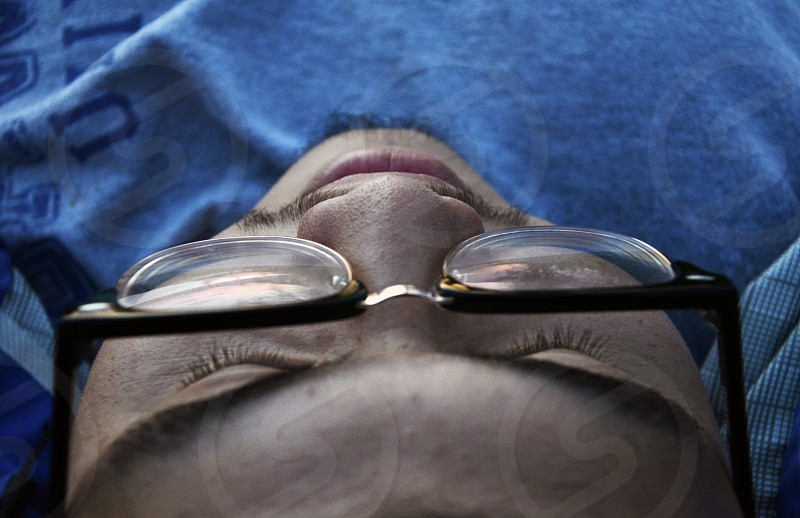 Closeup face man lying down thinking photo