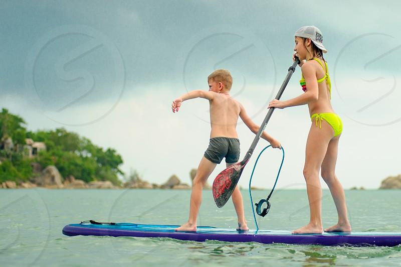 Two kids - boy and girl - having fun on a SUP board. photo