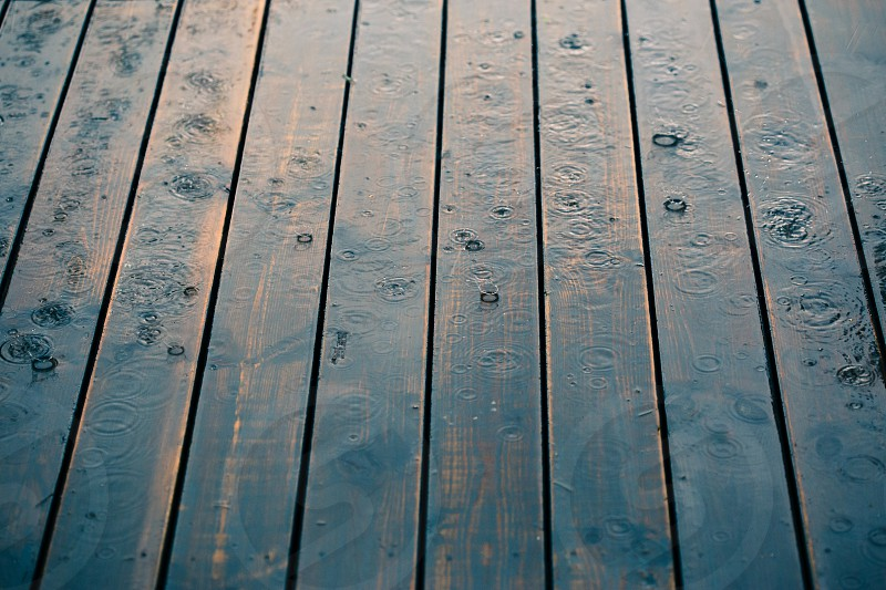 Closeup of wood planks while raining in perspective. Background of wooden natural surface and raindrops photo