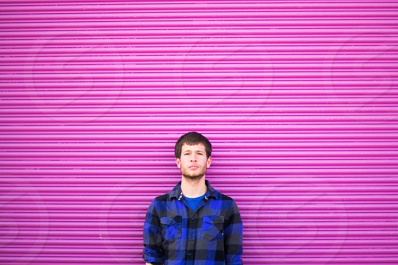 brunette man in grey blue and black plaid flannel shirt over blue crewneck shirt standing against pink ribbed metal wall photo