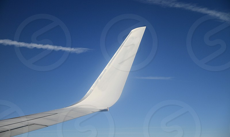 air plane wing with blue sky in the distance  photo