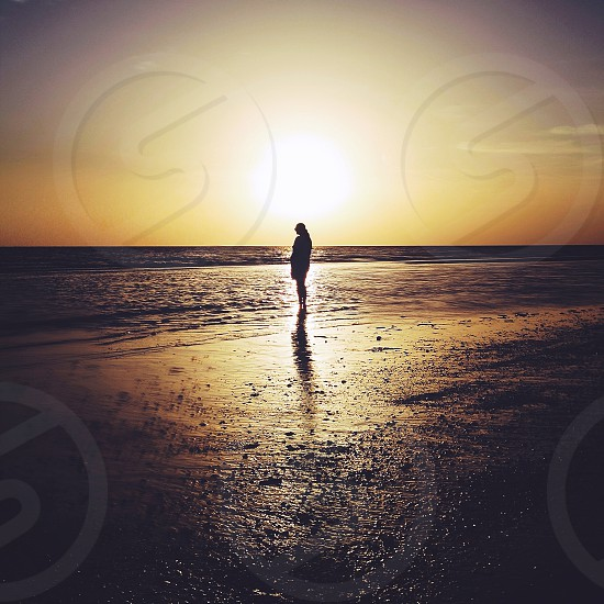 woman standing by the ocean at sunrise photo