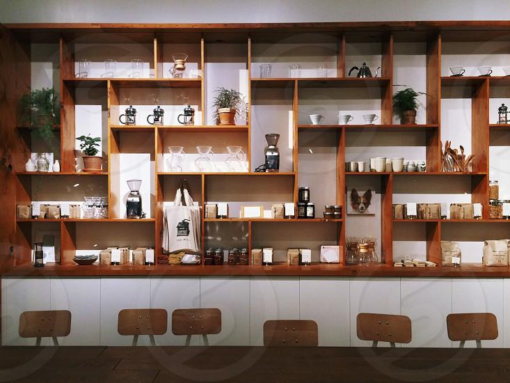 brown wood rectangular modular wall shelves above light wood chairs photo