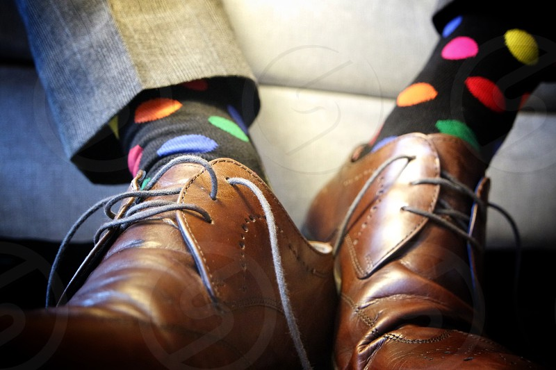 person wearing black oxford shoes and red yellow pink polka dotted socks photo