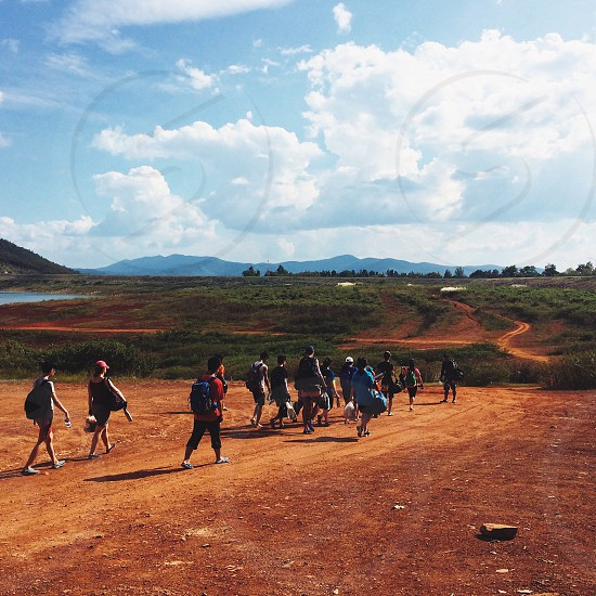 lake bank river bank crowed group people walking tourists sky blue soil orange camping field path hiking photo
