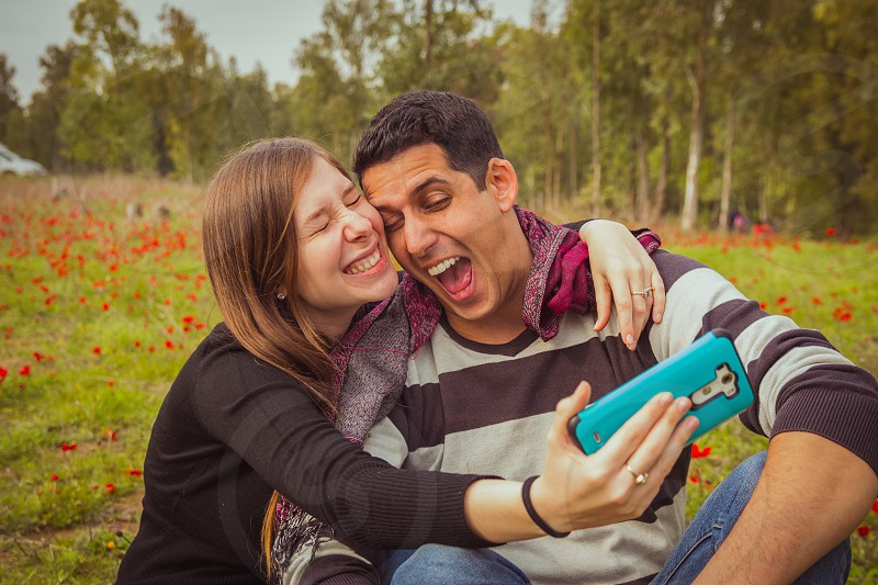 Couple doing silly and funny faces while taking selfie picture with their mobile phone in field of red poppies. photo