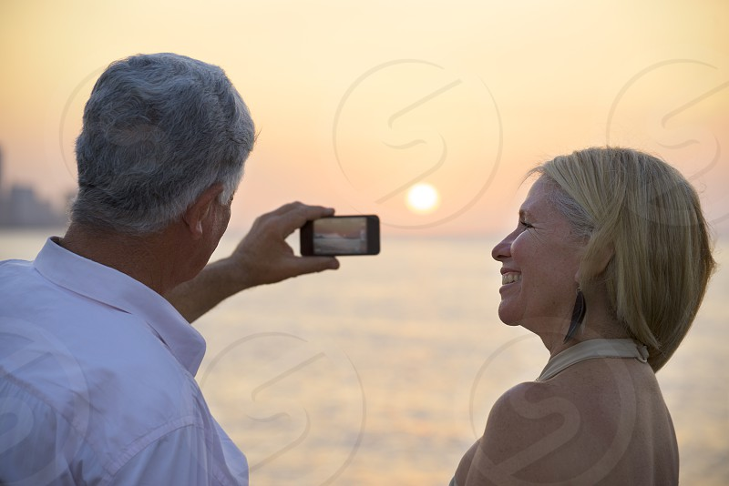 phone; smartphone; woman; couple; man; senior; vacation; 60s; adult; aged; caucasian; cuba; digital; elderly; female; fun; happy; hispanic; holidays; husband; latin american; leisure; male; mobile; ocean; old; people; persons; photo; photograph; picture; recreation; retired; retirement; sea; seniors; sightseeing; smiling; snap; snapshot; souvenir; summer; technology; together; tourist; travel; traveling; two; watching; wife photo
