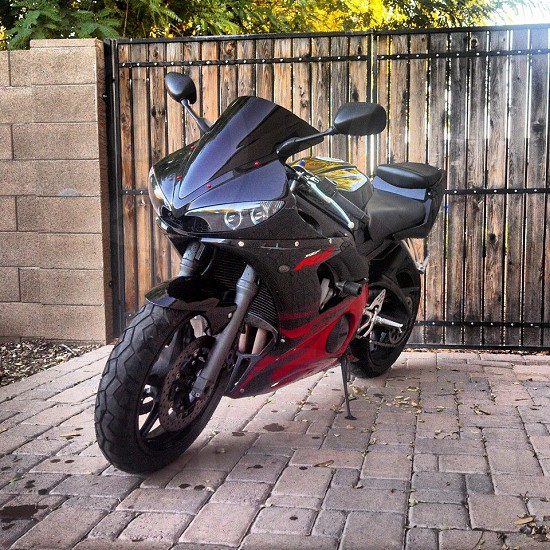Motorcycle parked in front of a gate. Standing still. Black and red sportsbike photo