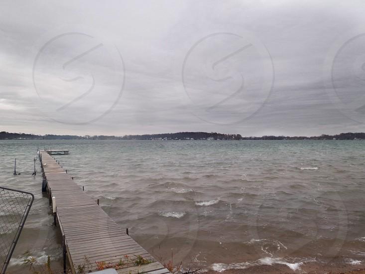 brown wooden dock beside body of water under dark sky photo