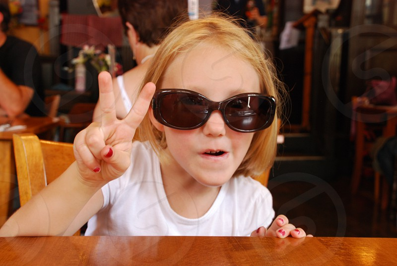Small girl wearing dark glasses in a London pub peace sign photo