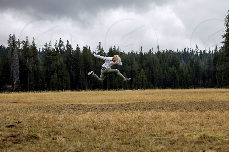 man jumping in a field by evergreens photo