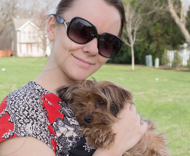 Young fashionable woman with sunglasses and cute dog outside on a sunny spring day. photo