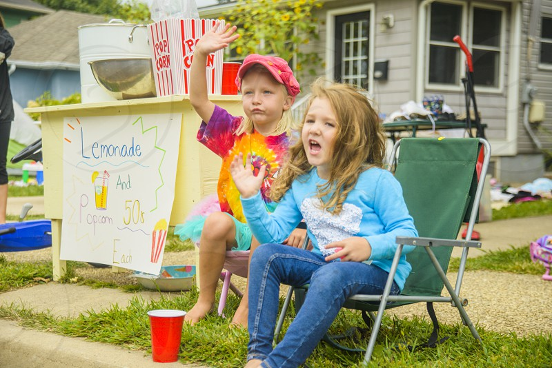 boy and girl sitting on green and grey chairs by a lemonade stand during daytime photo
