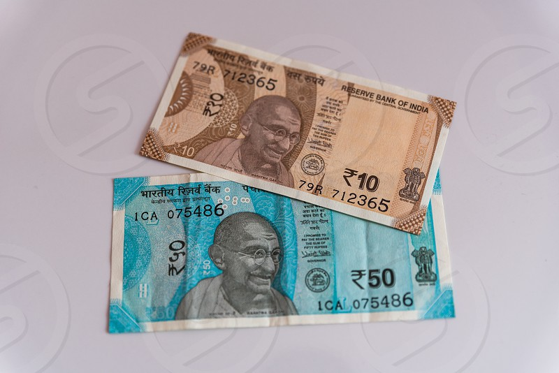 Indian currency notes of Rupees Fifty and Rupees Ten on white background photo