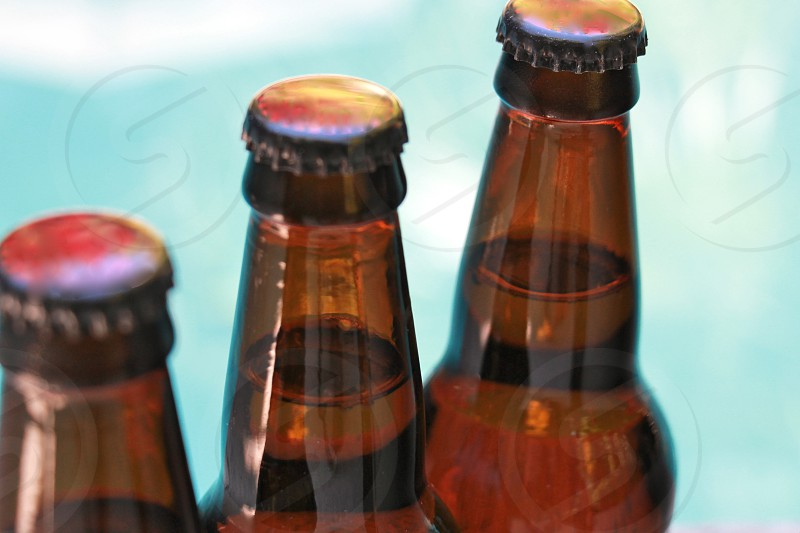 3 glass bottles with red caps in tilt shift lens photography photo