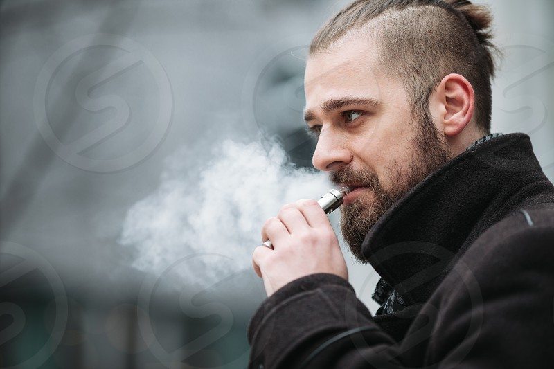 Men with beard hold and smoke his electronic cigarette outdoor in black grey backgraund photo