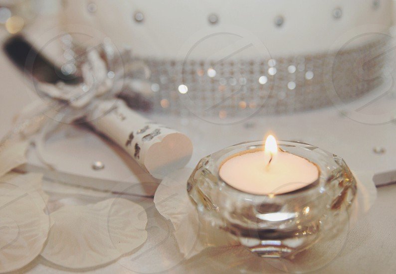white lighted candle on a clear glass candle holder photo