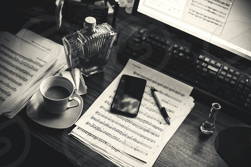 Details of a table of a composer music note sheets and computer and other lifestyle objects.  photo