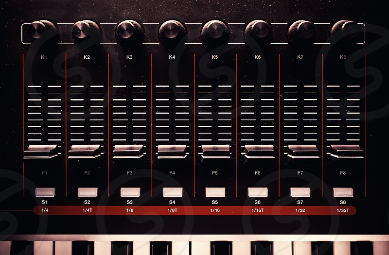 Sliders and knobs of a dusty modern midi controller.  photo