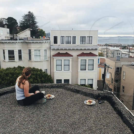woman in blue tank top and black pants sitting on top of building photo
