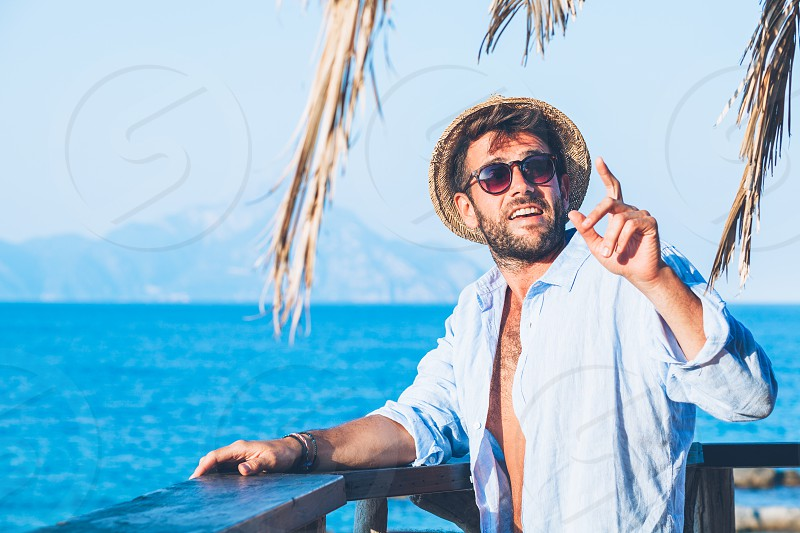 Young handsome man ordering at the beach bar photo