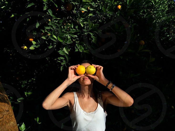 woman in orange tank top with two oranges held up for eyes photo