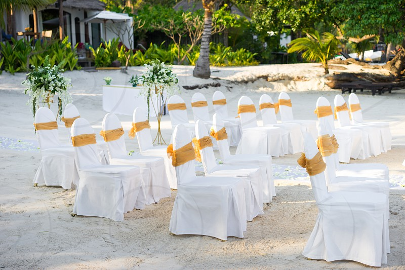 Beach wedding venue arrangement with spandex white cover chairs gold organza sash on the white sand photo