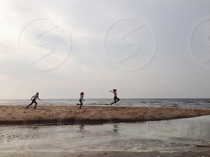 3 women walking through beach photo