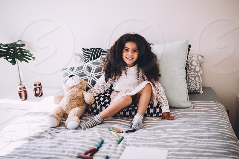 Little african girl sitting on bed with teddy bear smiling photo