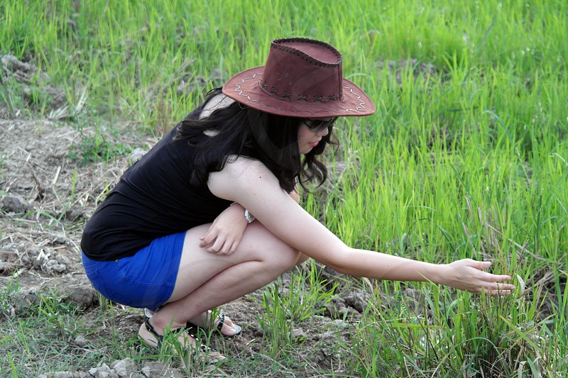 woman wearing brown hat black sleeveless shirt blue skirt sitting and holding green grass photo