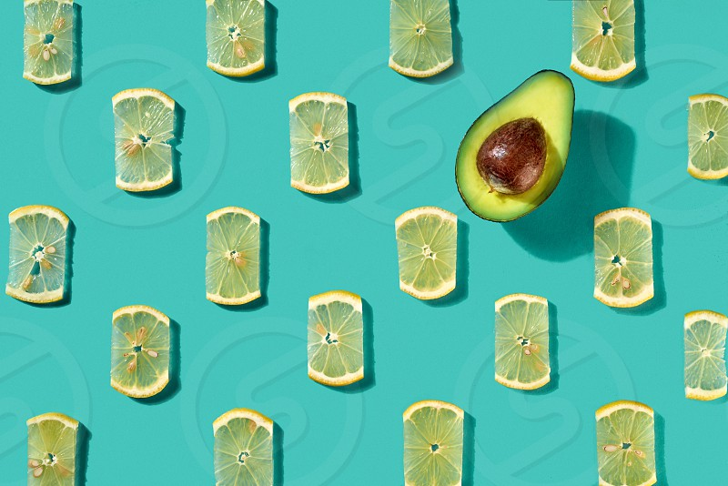 Half an avocado and juicy lemon slices on a blue background. Creative food pattern for layout. Flat lay photo