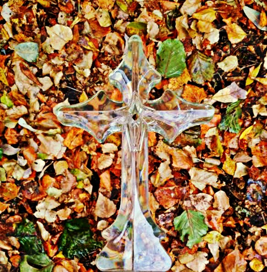 Autumn Leaves backdrop the iridescent Cross. photo
